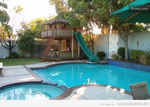 Decoración piscina exterior con casa madera y tobogán