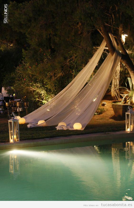 Decoración piscina exterior con velas y dosel
